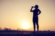 Runner drinks water after training