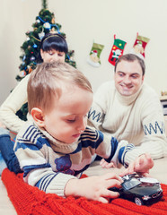 Boy playing with toy cars with his parents under the christmas t