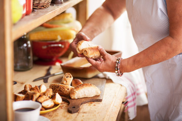 Senior woman remove baked rolls from oven