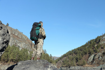 The man with a backpack standing at the mountain river