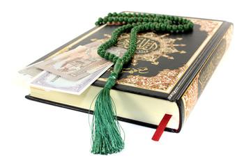 zugeschlagener Koran mit pakistanischer Währung