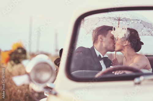 Bride and groom in a vintage car - 73879993