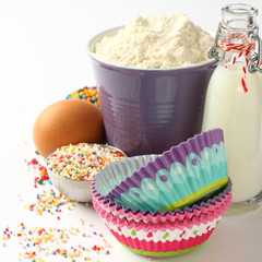 Cupcake cases and ingredients over white with copyspace