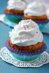 Cupcakes with white cream icing on blue wooden background