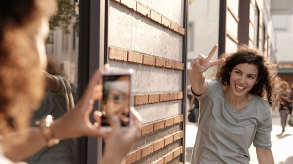 Young woman uses smartphone to take photo of friend waving in st