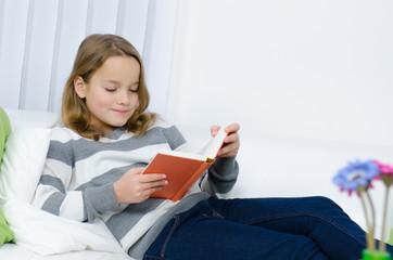 jugendliche liest gemütlich ein buch