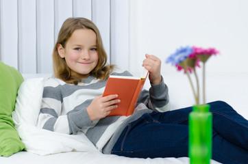 kind liegt mit lektüre auf dem sofa