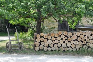 Brennholzstapel und Sackkarre