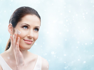 Woman applying cream on her face, winter background
