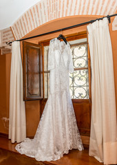Spanish style white wedding dress hanging from rail