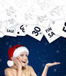 Pretty woman in Christmas cap gestures palm up special prices