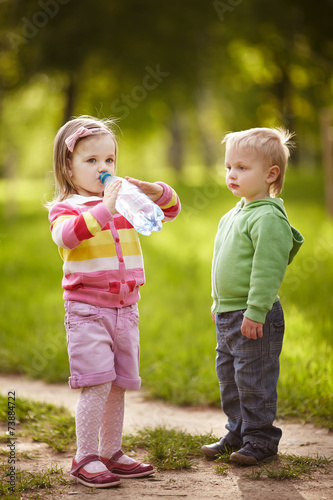 boy and girl drinking mineral water in park - 73884722