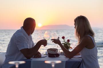 Couple on romantic date at beach restaurant on sunset