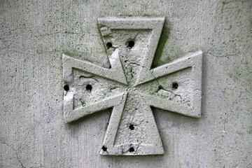 Kreuz mit Löchern auf einem Grabstein