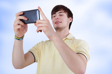 Young man with smiling eyes looking at his smartphone