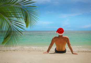Man on the tropical beach in Santa Claus hat