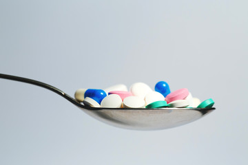 lots of colored tablets on a spoon.