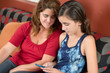 Teen girl using a cellphone with her mother by her side