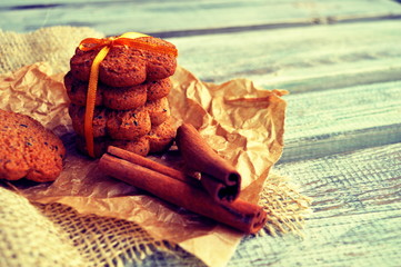 Cookies with cinnamon sticks on a wooden background