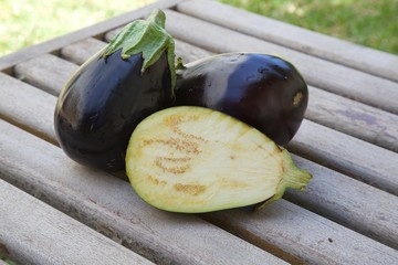 Two and one half eggplants on an old wooden surface