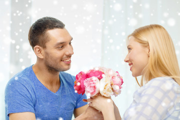 smiling man giving girlfriend flowers at home