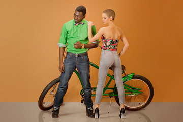 sexy couple in front of a bycicle on orange background