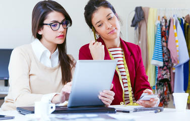 Two young businesswomen working with digital tablet in her offic