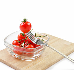 Cherry tomatoes in a glass bowl and fork with clipping path