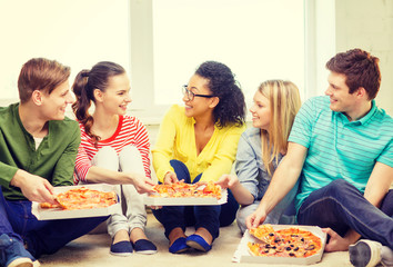 five smiling teenagers eating pizza at home