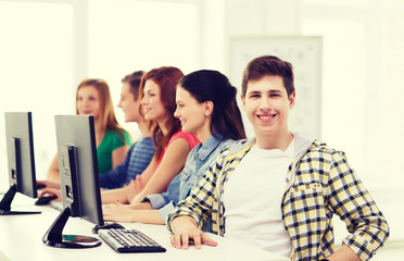 male student with classmates in computer class