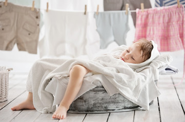 Sleeping little child into the bowl with clothes in the laundry