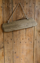 Blank  signboard  hanging from a nail on an old wooden oak wea