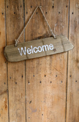 Welcome sign hanging from a nail on an old rustic wooden oak wea