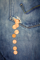 Money fall down from a hole in jeans pocket