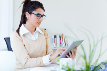 Young businesswomen working with digital tablet in her office.