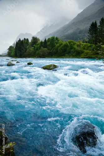 Milky blue glacial water of Briksdal River in Norway - 73891121