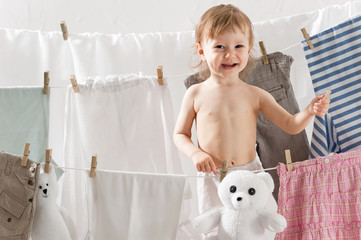 Little girl hangs laundry in the laundry