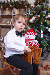 ittle boy in a white shirt and bow tie riding a wooden horse aro