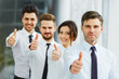 Successful young business people showing thumbs up