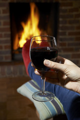 Woman With Glass Of Red Wine Relaxing By Fire