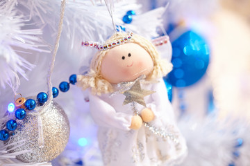 Christmas toys in the form of an angel hanging on the tree next