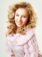 cheerful blond woman in a pink sweater. the winter season.