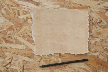 A sheet of distressed carton paper and pencil