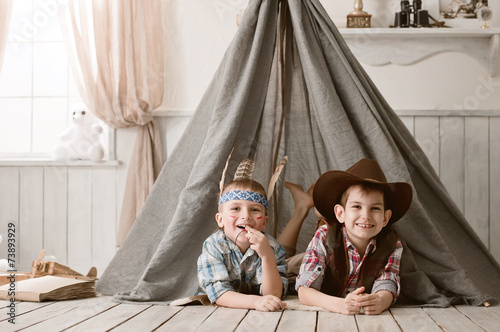 Boys as Indian and cowboy playing in her room - 73893929