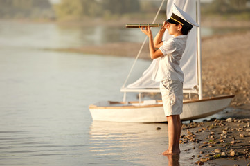 Boy captain looking through a telescope at the lake