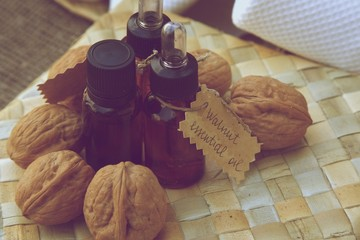 Bottle of walnut essential oil on the woven surface.