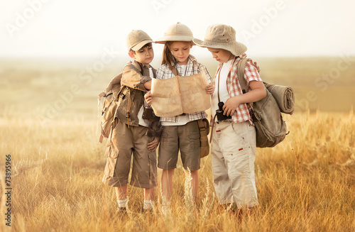 Group of kids travelers read a map at sunset