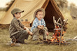 Two of children sitting around the campfire travelers - 73896141