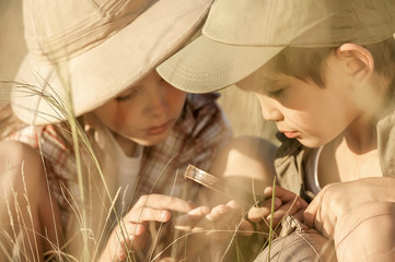 Two children explore insects and plants on earth