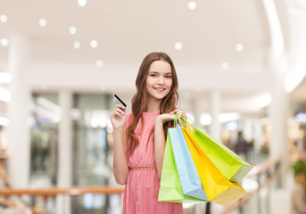 woman with shopping bags and credit card in mall